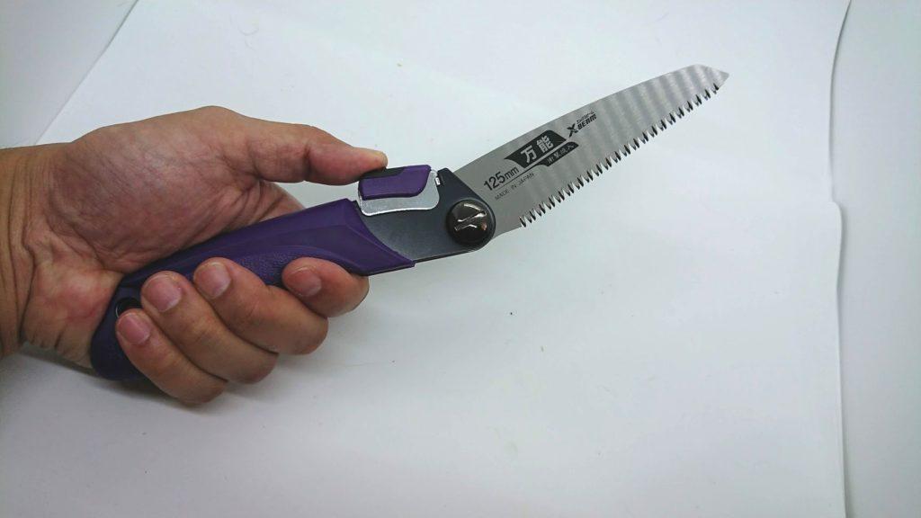 高儀「替刃式折込鋸 万能目」を畳むときはストッパーを押す。