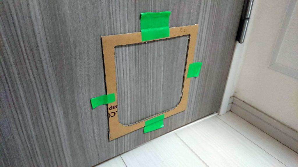 CEESC「4WAY ペットドア」の型紙をドアに貼ったところ。