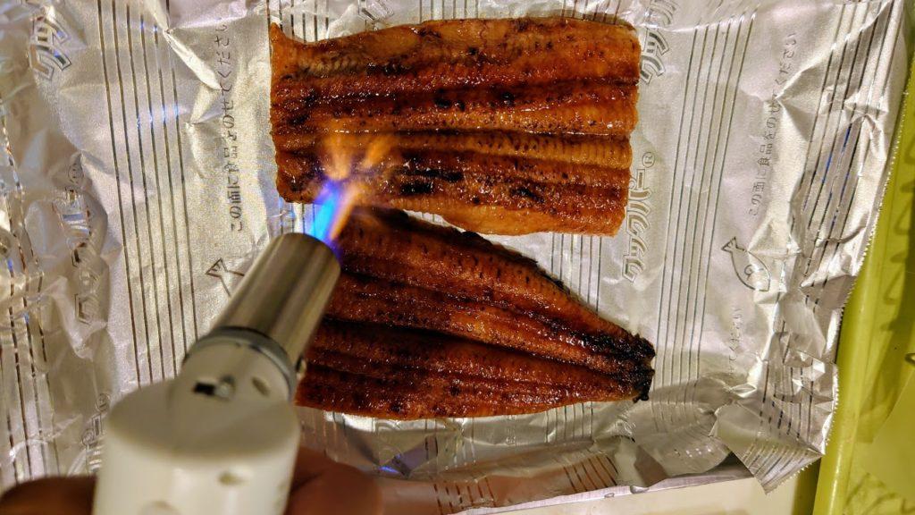 川口水産「国産超特大うなぎ蒲焼き」をバーナーで炙る。